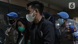 Polisi membawa Jennifer Jill (kedua kiri) untuk rilis kasus Narkoba di Polda Metro Jaya, Jakarta, Jumat (19/02/2021). Jennifer Jill ditetapkan sebagai tersangka kepemilikan barang bukti berupa 2 paket plastik kecil sabu-sabu dengan berat 0,39 gram beserta alat pengisap. (Liputan6.com/Herman Zakharia