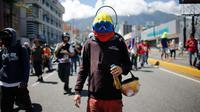 Seorang pengunjuk rasa memakai topeng berwarna bendera Venezuela, saat ikut serta dalam demonstrasi anti-pemerintah ke Mahkamah Agung di Caracas, Venezuela, Kamis, 6 Juli 2017. (AP Photo / Ariana Cubillos)