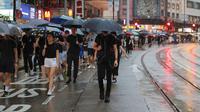 Pengunjuk rasa membawa payung saat menuju Victoria Park, Hong Kong, Minggu (18/8/2019). Puluhan ribu massa pro-demokrasi membawa payung saat hujan mengguyur Victoria Park dan sekitarnya. (AP Photo/Kin Cheung)