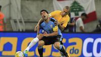 Luis Suarez (kiri) bertarung melawan pemain bertahan Brasil pada kualifikasi Piala Dunia 2018 zona CONMEBOL, Jumat (25/3/2016). (EPA/Sebastiao Moreira)