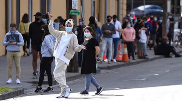 Warga mengantre di stasiun pengujian COVID-19 di Melbourne, Australia, Kamis (19/8/2021). Melbourne melewati 200 hari dalam lockdown keras sejak dimulainya pandemi COVID-19. (William WEST/AFP)