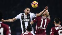 Bek Juventus, Giorgio Chiellini, duel udara dengan striker Torino, Simone Zaza, pada laga Serie A di Stadion Olympic, Turin, Sabtu (15/12). Torino kalah o-1 dari Juventus. (AFP/Marco Bertorello)