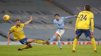 Gelandang Manchester City, Bernardo Silva (tengah) melepaskan tendangan ke gawang Brighton and Hove Albion dalam laga lanjutan Liga Inggris 2020/21 di Etihad Stadium, Rabu (13/1/2021). Manchester City menang 1-0 atas Brighton. (AFP/Martin Rickett/Pool)