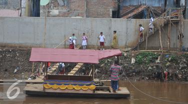 Sejumlah siswa SD saat ingin menaiki perahu eretan untuk berangkat ke sekolah di Sungai Ciliwung, Jakarta, Senin, (4/1). Usai libur panjang para siswa kembali beraktivitas mengikuti tahun ajaran 2016-2017. (Liputan6.com/Gempur M Surya)