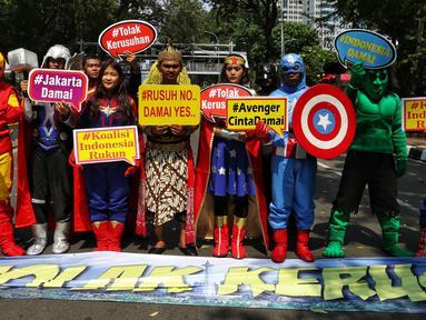 Sejumlah massa berpose mengenakan baju superhero melakukan aksi sebelum berjalan dari Patung Kuda menuju gedung Mahkamah Konstitusi (MK), Jakarta Pusat, Selasa (18/6/2019). Dalam aksinya mereka menyerukan perdamaian. (Liputan6.com/Johan Tallo)