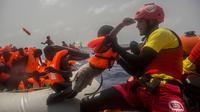 Petugas LSM Spanyol menyelamatkan anak imigran dari Afrika sub-Sahara di tengah Laut Mediterania, Selasa (25/7). Juru bicara penjaga pantai Italia mengatakan sekitar 260 migran telah diselamatkan dari perahu yang berbeda pada hari itu. (AP/Santi Palacios)
