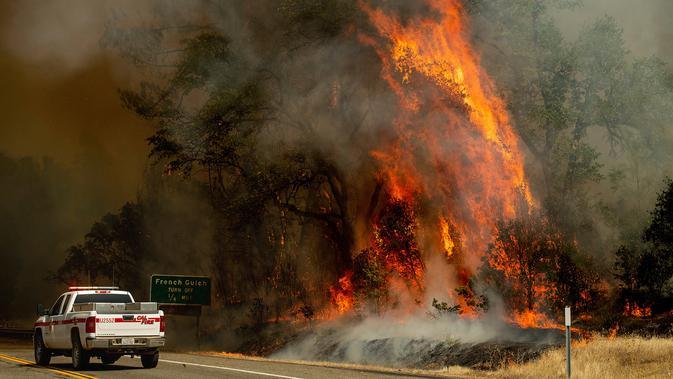Sebuah truk melintas dekat kobaran api dalam kebakaran hutan yang dijuluki Carr Fire di Whiskeytown, California, Jumat (28/7). Lebih  3.000 warga terpaksa meninggalkan rumah mereka di kawasan resor pegunungan akibat meluasnya kebakaran. (AP/Noah Berger)