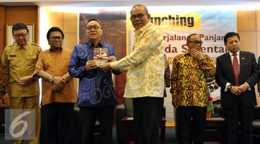 """Pengarang Buku """"Perjalanan Panjang Pilkada Serentak"""" sekaligus Ketua Komisi II Rambe Kamarul Zaman (ketiga kanan) memberikan buku kepada Ketua MPR Zulkifli Hasan, Jakarta, Senin (26/9). (Liputan6/JohanTallo)"""