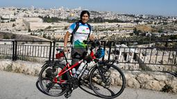 Pria Taiwan, Jacky Chen, berpose dengan sepedanya di Bukit Zaitun yang menghadap ke Kota Tua Yerusalem dan Kubah Batu pada 10 Juni 2019. Pria 40 tahun itu berharap bisa menjelajahi 100 negara dengan jarak 100.000 km sebelum mengakhiri petualangannya 3 tahun mendatang. (MENAHEM KAHANA/AFP)