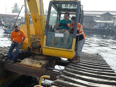 Menteri Koordinator Bidang Kemaritiman Luhut Binsar Panjaitan menaiki traktor menggelar gerakan aksi bersih di kawasan pesisir Cilincing, Jakarta Utara, Sabtu (6/4). Acara itu dalam rangka memperingati Hari Bumi. (Liputan6.com/Immanuel Antonius)
