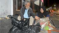 Soesilo Toer (kiri) saat sedang memulung sampah ditemani wartawan Jawa Pos Radar Kudus Noor Syafaatul Udhma di Blora baru-baru ini. (RADAR KUDUS PHOTO)