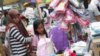 Seorang ibu bersama anaknya memilih keperluan sekolah di Pasar Asemka, Jakarta, Selasa (7/9/2019). Jelang dimulainya tahun ajaran baru, Pasar Asemka ramai dikunjungi warga untuk berbelanja keperluan sekolah. (Liputan6.com/Helmi Fithriansyah)