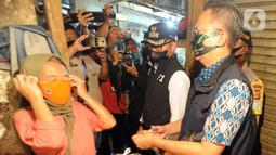Wali Kota Bogor Bima Arya (tengah) saat mengecek kepatuhan warga dalam menggunakan masker di Pasar Ciawi, Bogor, Kamis (10/9/2020). Kegiatan ini bagian dari kesepakatan antara Pemkot dan Pemkab Bogor dalam pengawasan penerapan protokol kesehatan di titik-titik perbatasan. (merdeka.com/Arie Basuki)