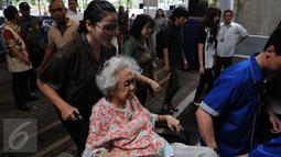 Seorang wanita didorong dengan kursi roda saat mengikuti Misa Natal di Gereja Katedral, Jakarta, Sabtu (24/12) Antusias para peserta misa ibadah natal kali ini diprediksi akan lebih ramai dibanding tahun sebelumnya. (Liputan6.com/Helmi Afandi)