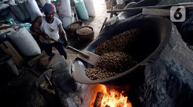 Pekerja mengolah kacang dengan media pasir di salah satu industri rumahan pembuatan kacang sangrai di Kawasan Keranggan, Tangerang Selatan, Selasa (11/8/2020). Kacang sangrai yang dipasarkan seharga Rp10.000 per kg itu mulai mengalami kenaikan pesanan dibanding bulan lalu. (merdeka.com/Dwi Narwoko)