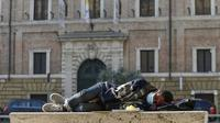 Pria memakai masker untuk mencegah terpapar virus corona COVID-19 saat tidur di bangku jalan di Roma, Italia, Rabu (8/4/2020). Berdasarkan data Worldmeters per Minggu (12/4/2020), jumlah kasus COVID-19 di Italia sebanyak 152.271 terinfeksi dan 19.468 meninggal. (Cecilia Fabiano/LaPresse via AP)