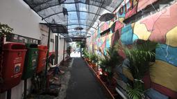 Aktivitas warga di gang di RT 13 RW 06, Jembatan Lima, Jakarta, Kamis (10/1). Warna-warni mural di pemukiman padat penduduk itu merupakan ide Aryanto selaku Ketua RT 13. (Merdeka.com/Iqbal Nugroho)