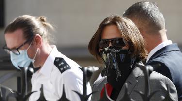 Aktor Johnny Depp memakai kacamata hitam dan syal saat menghadiri sidang pencemaran nama baik di Pengadilan Tinggi, London, Inggris, Selasa (21/7/2020). Johnny Depp menggugat tabloid The Sun atas artikel yang menyebut dirinya telah melakukan kekerasan terhadap sang istri. (AP Photo/Alastair Grant)