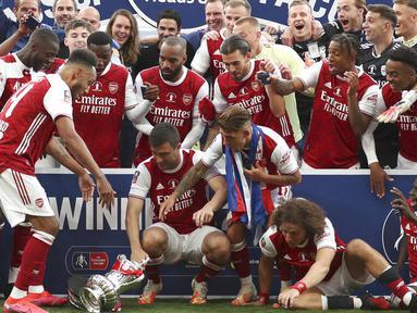 Ekspresi para pemain Arsenal ketika Piala FA terjatuh saat perayaan gelar juara di Stadion Wembley, London, Minggu (2/8/2020). Arsenal menjadi Juara Piala FA setelah menaklukkan Chelsea dengan skor 2-1. (Catherine Ivill/Pool via AP)