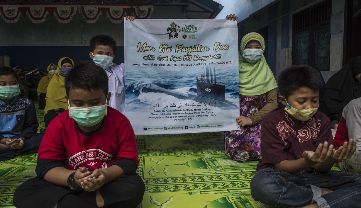Siswa dan guru berdoa untuk 53 awak kapal selam KRI Nanggala 402 yang hilang di perairan Bali, di sebuah sekolah Islam di Surabaya, Jumat (24/4/2021). Kapal selam KRI Nanggala-402 yang membawa 53 awak dilaporkan hilang kontak di perairan Bali, Rabu, 21 April kemarin. (Juni Kriswanto/AFP)