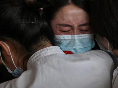 Staf medis dari Provinsi Jilin (tengah) memeluk perawat dari Wuhan setelah bekerja bersama menangani pandemi Covid-19 saat upacara pelepasan di Bandara Tianhe, Wuhan, provinsi Hubei, Rabu (8/4/2020). Pemulangan staf medis ini bersamaan dengan dicabutnya status lockdown Wuhan. (Hector RETAMAL/AFP)