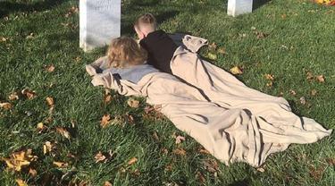 Mason (8) dan Maylan (5) menggelar selimut cokelat dan berbaring di atas makam ayahnya bernama Alfred David Brazel (Facebook/Kait Brazel)
