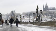 Orang-orang menyeberangi Jembatan Charles abad pertengahan setelah hujan salju pertama di Praha, Republik Ceko (3/12/2020). (AP Photo / Petr David Josek)