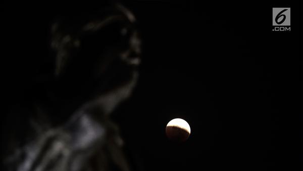 """Foto fenomena gerhana bulan total di kota Jakarta, Sabtu (28/7). Gerhana bulan total """"Micro Blood Moon"""" tersebut merupakan yang terlama pada abad ini dengan total waktu termasuk fase penumbra dan parsial selama enam jam lebih. (Liputan6.com/Johan Tallo)"""