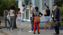 Orang-orang menggunakan ponsel mereka untuk terhubung ke internet melalui WiFi di sebuah taman di Havana, Rabu (5/12). Kuba merupakan salah satu negara terakhir di dunia yang masih belum menerapkan internet mobil. (YAMIL LAGE/AFP)