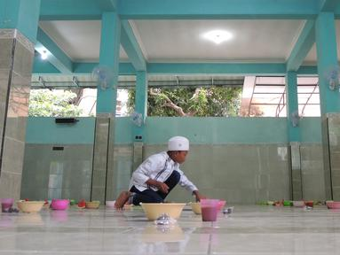 Pengurus Masjid Pekojan menyiapkan bubur India untuk menu buka puasa di serambi masjid, Semarang, Jawa Tengah, Kamis (17/5 ). Bubur India sebagai menu berbuka puasa di masjid ini sudah berjalan seabad lalu. (Liputan6.com/Gholib)