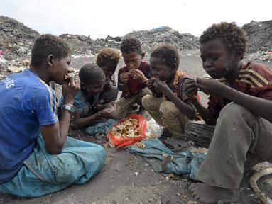 Sejumlah anak laki-laki makan bersama usai mengumpulkan sampah untuk didaur ulang di tempat pembuangan sampah di kota Houdieda, Yaman, Rabu (20/1). (REUTERS/Abduljabbar Zeyad)