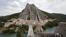 Pebalap Tour de France melewati kota Sisteron dengan bukit yang unik pada etape ke-29 dengan jarak tempuh 222,5 km dari Embrun menuju Salon-de-Provence, Prancis, (21/7/2017). (AP/Christophe Ena)