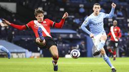 Pemain Manchester City, Phil Foden, melepaskan tendangan Saat melawan Southampton pada laga Liga Inggris di Stadion Etihad, Kamis (11/3/2021). City menang dengan skor 5-2. (Clive Brunskill/Pool via AP)