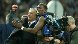 Jose Mourinho dengan Paul Pogba merayakan kemenangan Manchester United atas Ajax Amsterdam pada final Liga Europa di Friends Arena pada 24 Mei 2017. MU menang 2-0 atas Ajax berkat gol Pogba dan Henrikh Mkhitaryan. (AFP Photo/Soren Andersson)