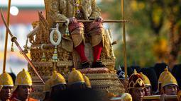 Raja Thailand Maha Vajiralongkorn diarak menggunakan tandu keliling Kota Bangkok, Thailand, Minggu (5/5/2019). Raja Vajiralongkorn yang bergelar Rama X dari Dinasti Chakri mengenakan jubah berhiaskan berlian. (AP Photo/Wason Wanichorn)