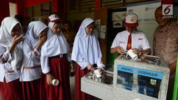 Para siswa antre mengambil air bersih langsung dari keran di SDN 03 dan SDN 04 Penjaringan, Jakarta, Jumat (22/3). Kegiatan ini bertujuan menyediakan air siap minum yang higenis dan bersih bagi siswa serta guru. (merdeka.com/Imam Buhori)