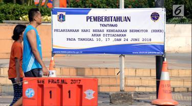 Warga melintas di depan spanduk pemberitahuan peniadaan pelaksanaan Hari Bebas Kendaraan Bermotor (HBKB) di Bundaran Hotel Indonesia, Jakarta, Minggu (3/6). Pelaksanaan HBKB akan ditiadakan pada 10, 17, dan 24 Juni 2018. (Liputan6.com/Helmi Fithriansyah)