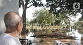 Seorang penjaga makam, Ismail (78) melihat kondisi banjir yang merendam pemakaman di Pulo Nangka, Jakarta, Minggu (23/2/2020). Selain permukiman, banjir merendam ribuan makam di Pulo Nangka hingga ketinggian mencapai 70 cm. (merdeka.com/Iqbal S. Nugroho)