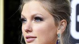 Penyanyi Taylor Swift berpose saat menghadiri Penghargaan Golden Globe Tahunan ke-77 di The Beverly Hilton Hotel di Beverly Hills, California (5/1/2020).  Taylor Swift  memilih gaun bunga biru dan kuning raksasa oleh Etro. (Frazer Harrison/Getty Images/AFP)