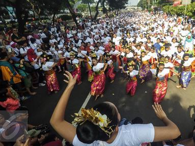 """Peserta mengikuti flashmob 1745 penari yang membawakan tarian tradisional di kawasan Senayan, Jakarta, Minggu (21/8). Kegiatan bertajuk """"Aku Indonesia-Bagimu Negeri Kami Menari"""" itu merupakan bagian dari perayaan HUT RI ke 71. (Liputan6.com/Fery Pradolo)"""