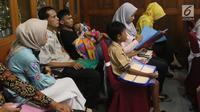 Orang tua murid tingkat SMA/SMK mengantre di Posko Pelayanan Peneriman Peserta Didik Baru (PPDB) Online tahun ajaran 2018 di SMKN 1 Budi Utomo, Jakarta, Kamis (28/6). Pendaftaran PPDB online tingkat SMA/SMK berakhir hari ini. (Liputan6.com/Arya Manggala)