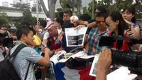 Pebalap Manor, Rio Haryanto, memberikan tanda tangan kepada fans di sela-sela rangkaian seri F1 GP Singapura, akhir pekan ini. (Rio Haryanto Media)