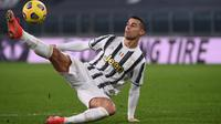 Penyerang Juventus, Cristiano Ronaldo menendang bola setelah kehilangan keseimbangan saat menghadapi Crotone dalam lanjutan Liga Italia di Allianz Stadium, Selasa dinihari (23/2/2021). Ronaldo menyumbang dua gol pada laga ini, sedangkan satu gol lagi disumbang Weston McKennie. (Marco BERTORELLO/AFP)