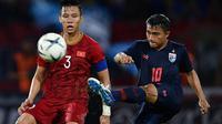 Duel pemain Vietnam, Que Ngoc Hai, dengan gelandang Timnas Thailand, Chanathip Songkrasin, saat kedua tim bertemu di kualifikasi Piala Dunia 2022 di Thammasat Stadium (5/9/2019).  (AFP/Chalinee Thirasupa)