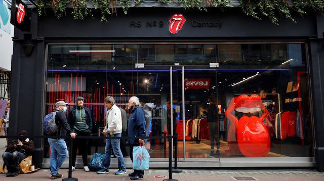 Orang-orang mengantre untuk memasuki toko andalan The Rolling Stones yang baru sebelum hari pertama pembukaannya di London, Rabu (9/9/2020). Rolling Stones membuka membuka toko pertamanya di 9 Carnaby Street. (Tolga Akmen / AFP)