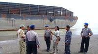 Kapal tongkang bernomor lambung PST.115 Batam/GT. 4334 /6382i PPM 2014/300 Feet ditemukan terdampar tanpa kru atau ABK di Pantai Pemalang. (Foto: Liputan6.com/Polres Pemalang/Muhamad Ridlo)