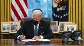 Presiden Amerika Serikat Joe Biden menandatangani Perintah Eksekutif yang membatalkan larangan bagi transgender untuk masuk militer AS pada era Donald Trump di Kantor Oval Gedung Putih, Washington, Senin (25/1/2021). (AP Photo/Evan Vucci)