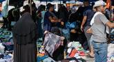 Seorang wanita Palestina berbelanja pakaian di sebuah pasar tradisional yang kembali dibuka setelah pelonggaran karantina wilayah COVID-19  di kamp pengungsi Nuseirat di Jalur Gaza tengah, Senin (13/7/2020). (AFP/Mohammed Abed)