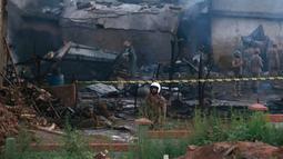 Pejabat militer Pakistan memeriksa lokasi kecelakaan pesawat di Rawalpindi, Pakistan, Selasa (30/7/2019). Kecelakaan menyebabkan 12 orang tewas dan memicu kebakaran besar yang melanda beberapa rumah. (AP Photo/Anjum Naveed)