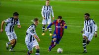 Pemain Barcelona Lionel Messi (kedua kanan) mengontrol bola yang dikelilingi para pemain Levante pada pertandingan La Liga Spanyol di Stadion Camp Nou, Barcelona, Spanyol, Minggu (13/12/2020). Barcelona menang 1-0. (AP Photo/Joan Monfort)